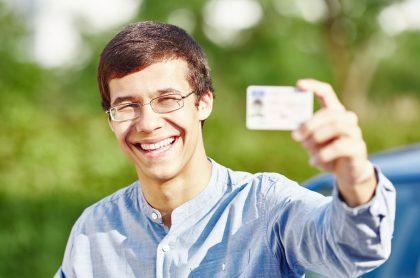 Imagen de un joven con su licencia de conducción, que ilustra nota del paso a paso para sacarla en Colombia