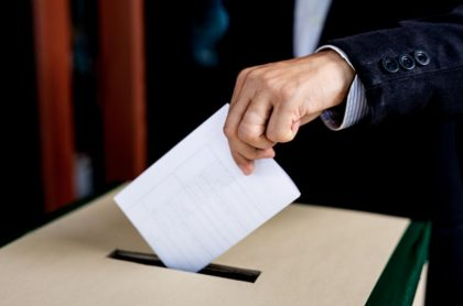 Persona deja su voto en una caja, ilustra nota de alcalde reelegido a pesar de estar muerto