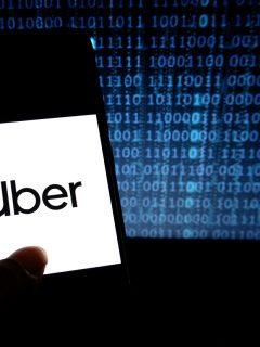 Celular con imagen de Uber y código binario. SIC reitera orden a Uber sobre protección de datos personales.