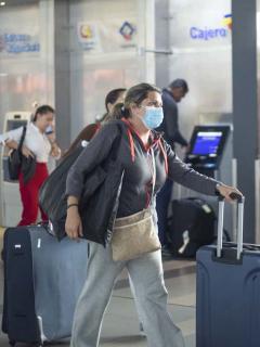 Imagen de viajera usando tapabocas en aeropuerto para ilustrar nota sobre las medidas de bioseguridad antes, durante y después de un vuelo