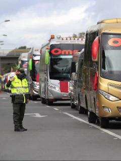 Imagen de policía y buses intermunicipales para ilustrar nota sobre los protocolos de seguridad vial para viajar en la semana de receso
