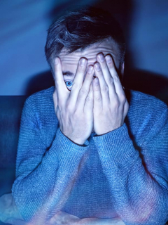 Hombre asustado viendo películas de terror, que son muy comunes en Halloween para ver en Netflix, HBO y Amazon Prime