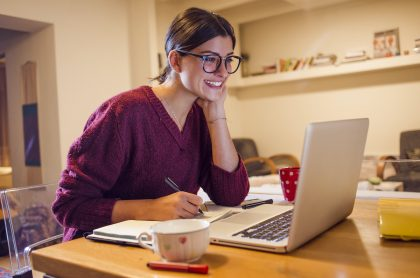 Imagen de mujer sonriendo mientras ve su computador para ilustrar nota sobre qué foto se debe usar en LinkedIn para buscar empleo