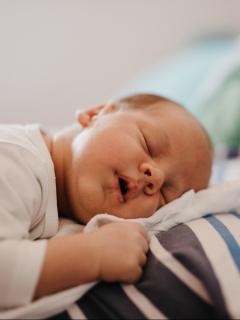 Foto de bebé durmiendo con su papá, a propósito de los nombres de niño y niña que significan luz y esperanza