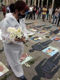 Una mujer asiste a un acto de homenaje por las víctimas durante la pandemia de COVID-19.