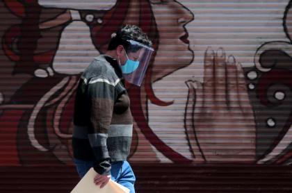 Hombre caminando con tapabocas en México, uno de los países de Latinoamérica que más se van a demorar en recuperarse de la pandemia