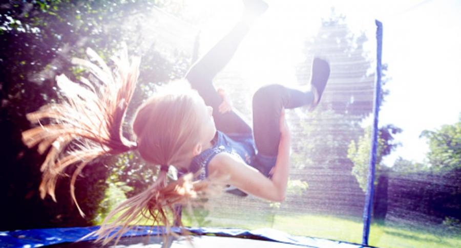 Imagen de niña saltando en trampolín bajo el sol
