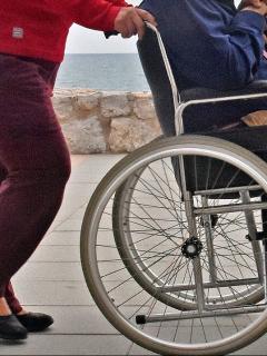 Imagen de referencia de una mujer llevando a un anciano en silla de ruedas.