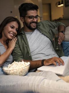 Pareja viendo una película en un computador para ilustrar nota sobre mejores sitios de Internet para ver película y series gratis
