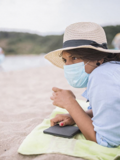 Mujer en la playa con tapabocas para ilustrar nota sobre el contagio de COVID-19 en el mar y en las piscinas