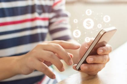 Persona con celular en las manos y signos de dinero para ilustrar nota sobre aplicaciones para ganar dinero