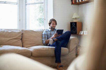 Hombre mira tableta, ilustra nota de empresa que pagará millonada por navegar en Internet