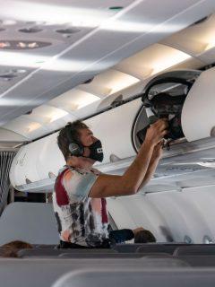 Pasajero de avión usando tapabocas para ilustrar nota sobre estudio que dice que viajar en avión es más seguro que salir a comer