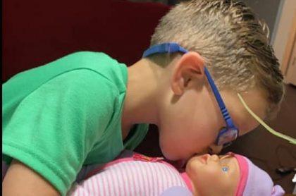 """Niño jugando con una muñeca que le pidió a su madre para aprender a """"ser un gran padre""""."""
