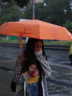 Joven con sombrilla en Bogotá, ilustra nota sobre localidades que se verán más afectadas por las lluvias esta semana