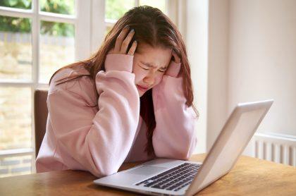 Joven angustiada frente al computador para ilustrar nota sobre qué es cyberbullying y casos