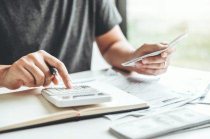 Persona usando calculadora para ilustrar nota sobre créditos con menos intereses