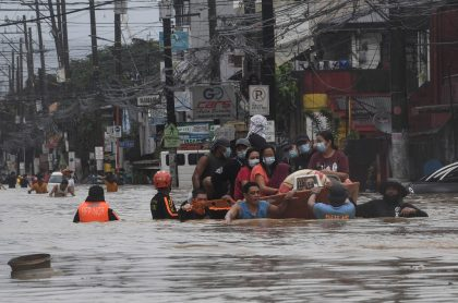 Inundaciones en Filipinas por huracán Vamco, ilustra nota de hombre que camina por cables de alta tensión para conseguir comida