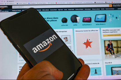 Imagen de persona que posa con un celular que muestra el logotipo de Amazon, frente a una pantalla de computador, ilustra artículo Farmacia digital de Amazon hace temer fin de droguerías.