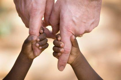 Niños afro toman de la mano a pareja blanca, ilustra nota de pareja se arrepiente de adoptar hermanos y los dejan en policía