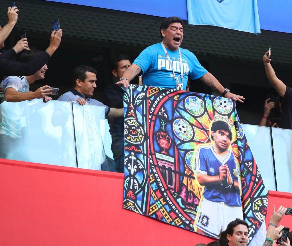 Diego Maradona cargando un cartel donde se le dibuja como un dios / Getty Images