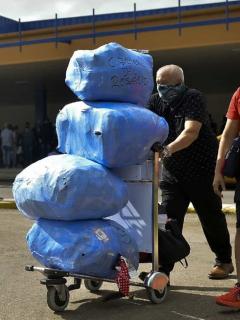 Cubanoamericanos cargan equipaje cuando salen del Aeropuerto Internacional José Martí, de La Habana.