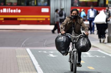 Persona en bicicleta con tapabocas en Bogotá ilustra nota sobre el segundo pico de coronavirus en la capital