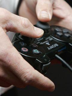 hombre jugando PlayStation (imagen de referencia).