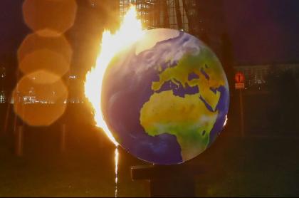Un mundo en llamas, para alertar sobre el calentamiento global, es usado por activistas del grupo ambientalista Koala Kollektiv, durante una protesta frente a la sede del Banco Central Europeo (BCE) en Frankfurt am Main, Alemania, el 21 de octubre de 2020.