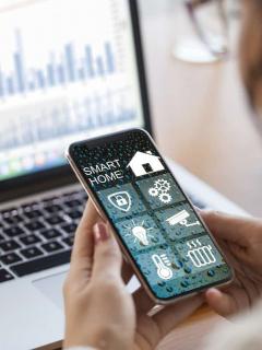 Mujer usando aplicación de hogar inteligente para ilustrar nota sobre 'gadgets' más deseados en las casas