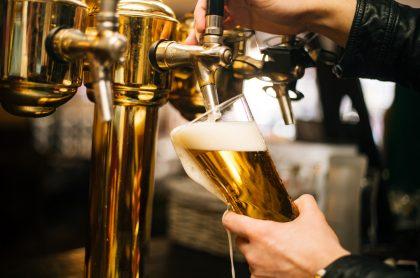 Mesero sirviendo cerveza ilustra nota sobre restricción a la venta de licor en lugares donde hay alta ocupación de camas UCI