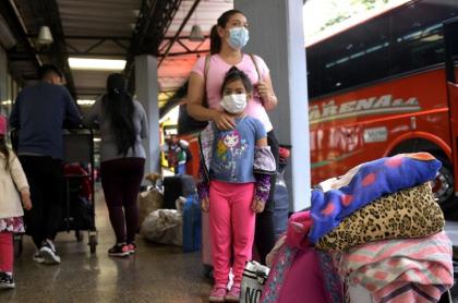 Viajeros antes de subirse a un bus, en plena pandemia.