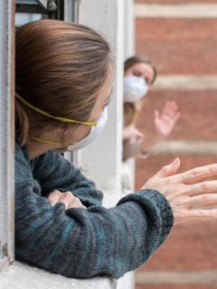 Mujeres se saludan a la distancia en medio de la pandemia, ilustran nota de las palabras más usadas en el año