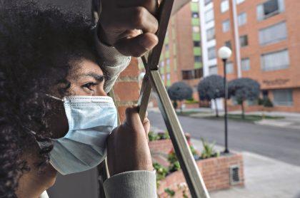 Hombre asomado en ventana de su casa usando tapabocas. Imagen de referencia para ilustrar cuáles son las restricciones que regirán en 3 localidades de Bogotá por cuarentena estricta.