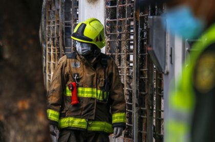 Uno de los bomberos del rescate a las fueras de la casa incendiada.