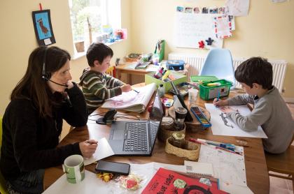 Imagen de mujer trabajando al lado de sus hijos ilustra artículo Teletrabajo: riesgo de borrar frontera trabajo-vida privada