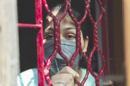 Imagen ilustrativa de una mujer con tapabocas y encerrada, a propósito del toque de queda en Cundinamarca, donde en Girardot, Fusa y Facatativá es total.