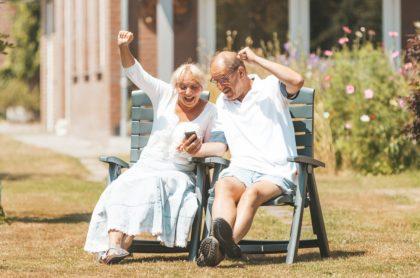 Pareja celebra mirando celular, ilustra nota de mujer que gana lotería al apostar durante 20 años números que sonó esposo