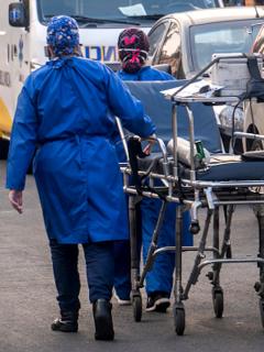 Profesionales de la salud transportan a un paciente de coronavirus.