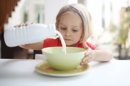 Niña tomando leche, producto que en Colombia está siendo rendido con lactosuero