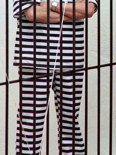Imagen de hombre con traje de rayas detrás de una rejas ilustra artículo Cadena perpetua para violadores de niños podría caerse por un vicio