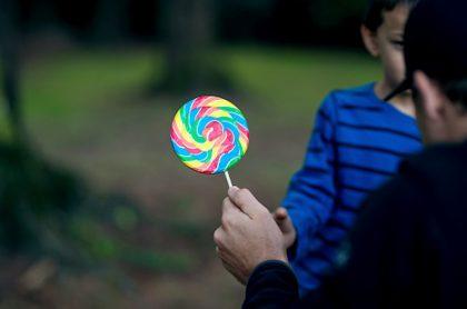 Adulto le ofrece dulces a un niño.