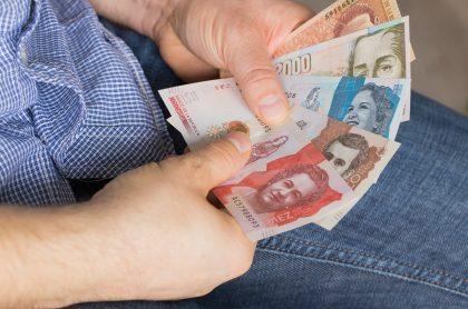 Hombre contando dinero. Imagen ilustrativa del pago del impuesto predial en Bogotá
