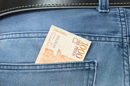Billete de mil pesos en un bolsillo.