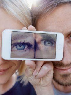 Hombre y mujer con celular en los ojos, ilustra nota de nuevo reto viral de ilusión óptica: ¿Cuántos colores ve?