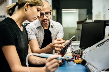 Técnico guiando a una joven aprendiz sobre la reparación de equipos técnicos en un taller. Imagen de referencia para ilustrar que el Sena abrió una convocatoria para estudiar carreras técnicas y tecnológicas de forma virtual en Colombia.