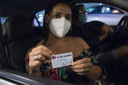 Persona mostrando certificado de vacunación ilustra la nota sobre que el Ministerio de Salud confirmó que Chille llegó este lunes a los dos millones de vacunados contra el coronavirus.