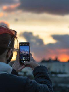 Foto de mujer  con su celular ilustra nota sobre ¿Cuáles son las mejores aplicaciones para editar fotos?
