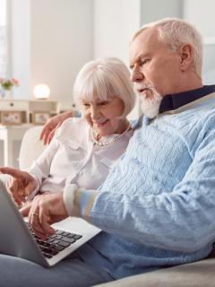 Pareja sentada, buscando algo en internet. Imagen ilustrativa a 'Mi planilla' la herramienta para hacer pagos de la Seguridad Social.