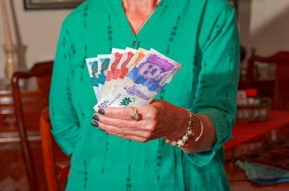 Mujer con la nueva familia de billetes. Imagen ilustrativa de quiénes son los personajes que aparecen en los billetes colombianos.